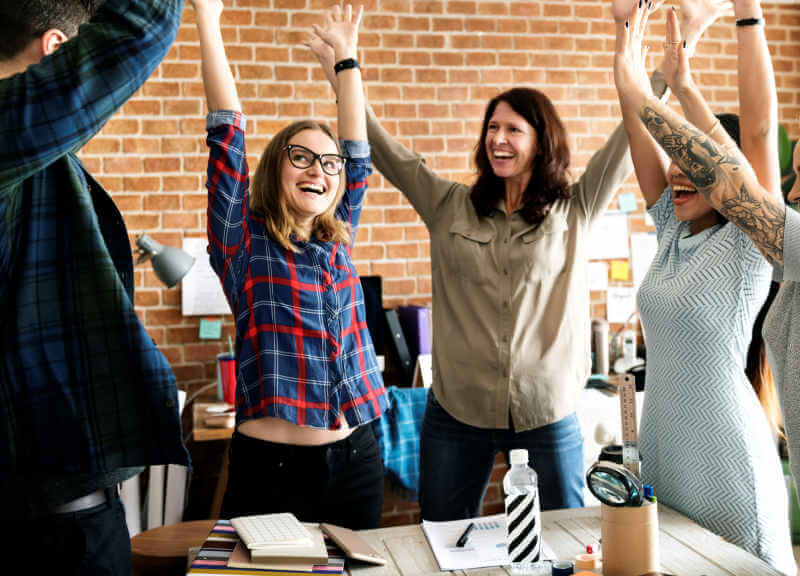 Five people in an office celebrating completing their PMP Exam Prep course from Versatile