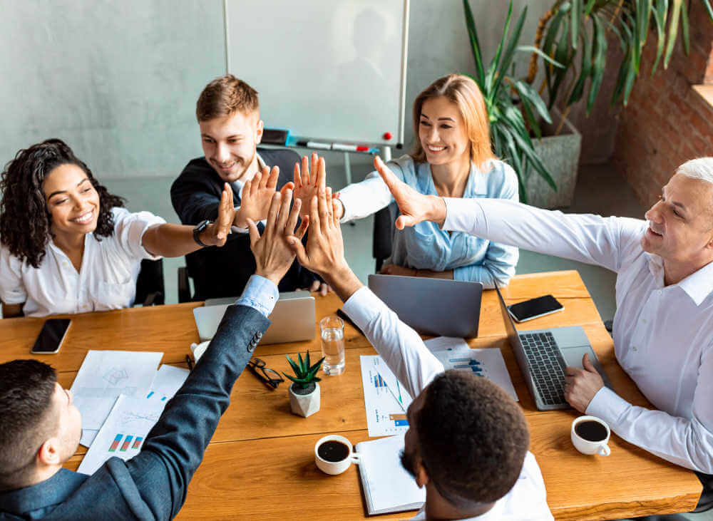 """A group of business people """"high-five"""" at a wooden table while participating in project management training for non-project managers"""