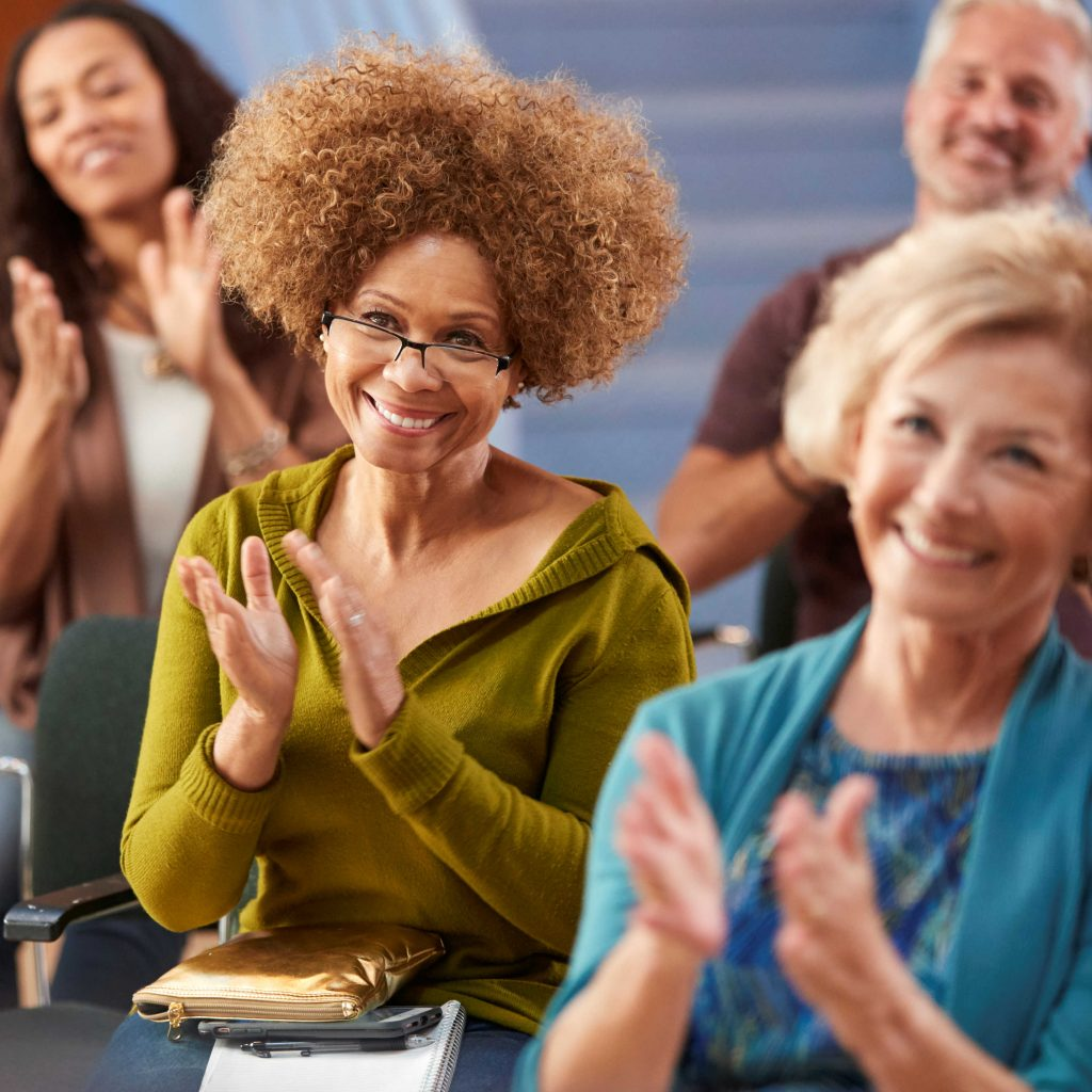 Business people clapping during a project management training by The Versatile Company