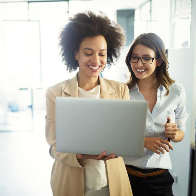 Two business women with a computer watching a Versatile Company video.